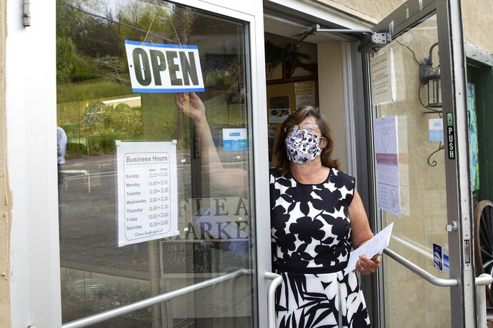 Hawley Antique Exchange manager Angela Gayes Soden turns the store's open sign in Hawley, Pa. on Friday, May 22, 2020. Many Wayne County businesses opened on Friday for the first time since March as the county moved to the yellow phase of reopening after the COVID-19 shutdown of non-essential businesses. (Christopher Dolan/The Times-Tribune via AP)