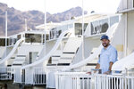 Chad Taylor, director of sales and marketing for Lake Mead Mohave Adventures, poses by houseboats at the Callville Bay Marina in the Lake Mead National Recreation Area Tuesday, Sept. 14, 2021 in Las Vegas.  Some businesses that depend on the Colorado River caught a wave of customers after coronavirus pandemic closures closed schools and offices. Taylor says that receding water levels at Lake Mead, the river's drought-stricken reservoir, have him constantly moving docks farther into Callville Bay. (Steve Marcus/Las Vegas Sun via AP)