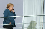 German Chancellor Angela Merkel makes a telephone call on a balcony of the Chacellery in Berlin, Germany, Friday, Sept. 20, 2019. The German government is scrambling to agree a package of measures for tackling global warming, as protesters prepare to stage rallies across the country demanding decisive action against climate change. (Kay Nietfeld/dpa via AP)