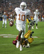 FILE - In this Jan. 4, 2006, file photo, Texas quarterback Vince Young rushes for the game-winning touchdown against Southern California during the Rose Bowl college football game in Pasadena, Calif. USC's run at No. 1 ended in the 2006 Rose Bowl, which was also one of the best games of the decade. Texas _ led by coach Mack Brown and quarterback Vince Young _ topped the Trojans 41-38 in a back-and-forth thriller. (AP Photo/Paul Sakuma, File)