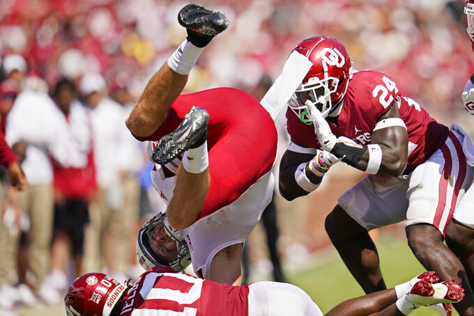 Nebraska tight end Austin Allen (11) is upended by Oklahoma safety Pat Fields (10) as linebacker Brian Asamoah (24) moves in during the first half of an NCAA college football game, Saturday, Sept. 18, 2021, in Norman, Okla. (AP Photo/Sue Ogrocki)