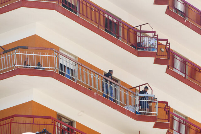 Residents stand on a balcony of an apartment complex where dozens of COVID-19 cases have been registered among a community of Bulgarian farm workers, in Mondragone, in the southern Italian region of Campania, Friday, June 26, 2020. The governor of the region is insisting that the farm workers should stay inside for 15 days, not even emerging for food, and that the national civil protection agency should deliver them groceries. (AP Photo/Riccardo De Luca)