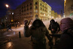 Anti-government protesters are sprayed by a water cannon as they clash with the riot police during ongoing protests in Beirut, Lebanon, Wednesday, Jan. 22, 2020.  Lebanon's new government held its first meeting Wednesday, a day after it was formed following a three-month political vacuum, with the prime minister saying his Cabinet will adopt financial and economic methods different than those of previous governments.  (AP Photo/Hassan Ammar)