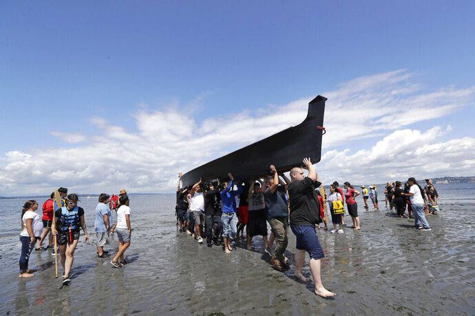 Canoe pullers and volunteers heft a canoe up the beach during a stop on the annual tribal canoe journey through the Salish Sea Thursday, July 18, 2019, in Seattle. About 20 canoes from Northwest Native coastal tribes landed Thursday at Alki Beach on one of several legs of the canoe journey that gathers other canoe families from host tribes as they travel to a final landing, this year near Bellingham, Wash., at the Lummi Nation. (AP Photo/Elaine Thompson)