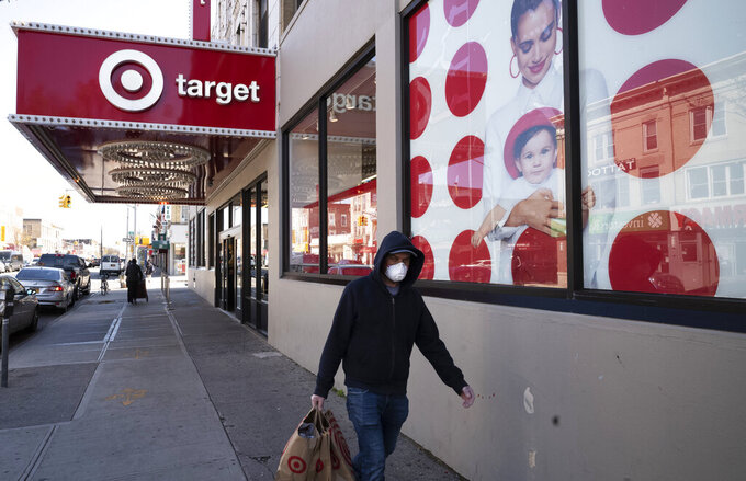 FILE - In this April 6, 2020 file photo, a customer wearing a mask carries his purchases as he leaves a Target store during the coronavirus pandemic, in the Brooklyn borough of New York.  Target extended its strong sales streak through the holiday quarter and grabbed business from rivals. The Minneapolis-based discounter reported Tuesday, March 2, 2021, that it profit soared 66%, while sales jumped 21% for its fiscal fourth quarter. (AP Photo/Mark Lennihan, File)