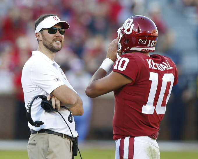 Oklahoma head coach Lincoln Riley, left, talks to quarterback Austin Kendall (10) in the second half of an NCAA college football game against Kansas State in Norman, Okla., Saturday, Oct. 27, 2018. (AP Photo/Sue Ogrocki)