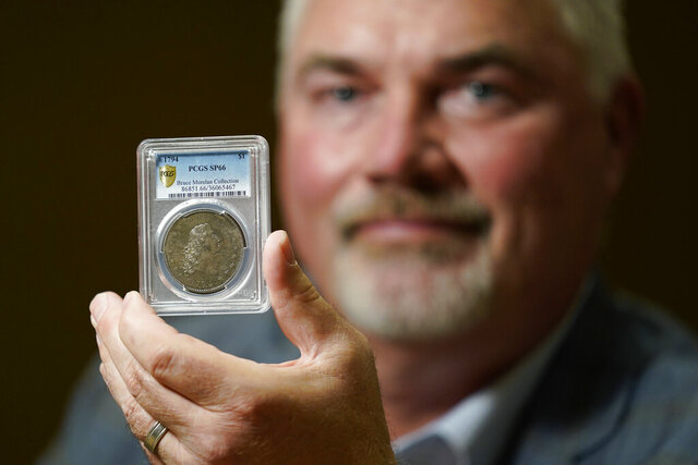 Bruce Morelan poses for a portrait holding a rare 1794 U.S. silver dollar, said to be among the first ever minted, Thursday, Aug. 6, 2020, in Las Vegas. Morelan, owner of the silver dollar said to be among most expensive ever sold, is preparing to put the coin up for public auction in Las Vegas. (AP Photo/John Locher)