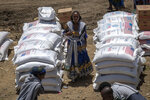 An Ethiopian woman stands by sacks of wheat to be distributed by the Relief Society of Tigray in the town of Agula, in the Tigray region of northern Ethiopia Saturday, May 8, 2021. A high-level U.N.-led committee that focuses on rapid responses to humanitarian crises estimates that some 350,000 people in Ethiopia's embattled Tigray region are facing famine conditions, a U.N. official said late Wednesday, June 9, 2021. (AP Photo/Ben Curtis)