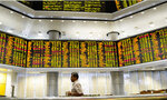 A visitor walks in front of private stock trading boards at a private stock market gallery in Kuala Lumpur, Malaysia, Friday, Dec. 7, 2018. Asian shares were mostly higher Friday after gains on Wall Street but investors continued to watch for news about U.S.-China trade friction. (AP Photo/Yam G-Jun)