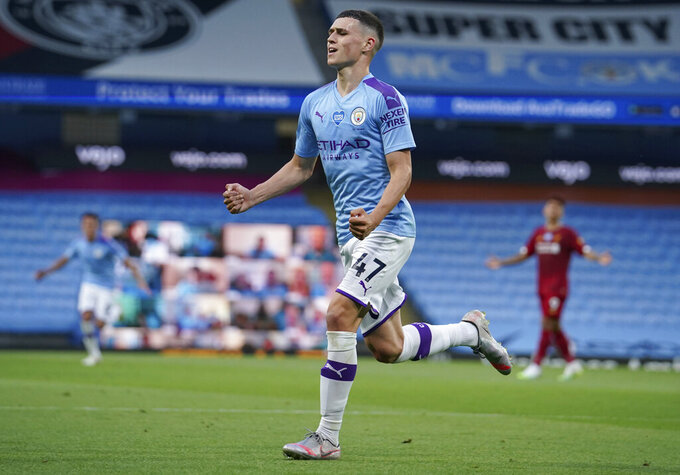 Manchester City's Phil Foden celebrates after scoring his team's third goal during the English Premier League soccer match between Manchester City and Liverpool at Etihad Stadium in Manchester, England, Thursday, July 2, 2020. (AP Photo/Dave Thompson,Pool)