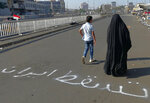 People walk by an Arabic sentence writing on the asphalt reads