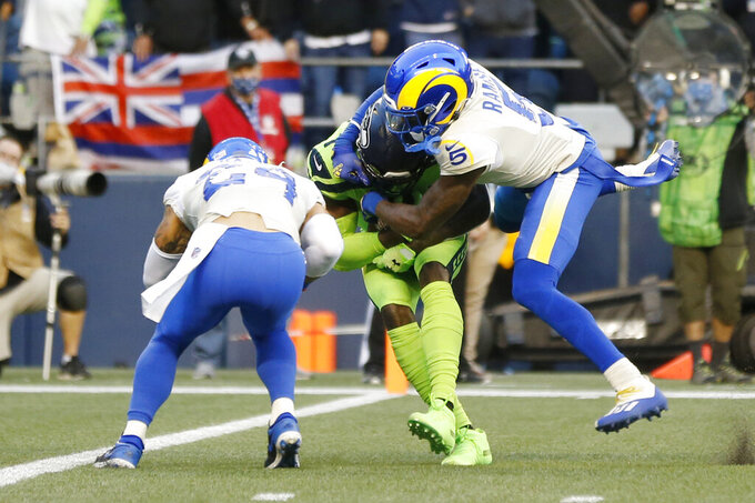 Seattle Seahawks wide receiver DK Metcalf, center, is tackled by Los Angeles Rams cornerback Jalen Ramsey as Rams' Taylor Rapp (24) moves in as Metcalf scores a touchdown during the first half of an NFL football game, Thursday, Oct. 7, 2021, in Seattle. (AP Photo/Craig Mitchelldyer)