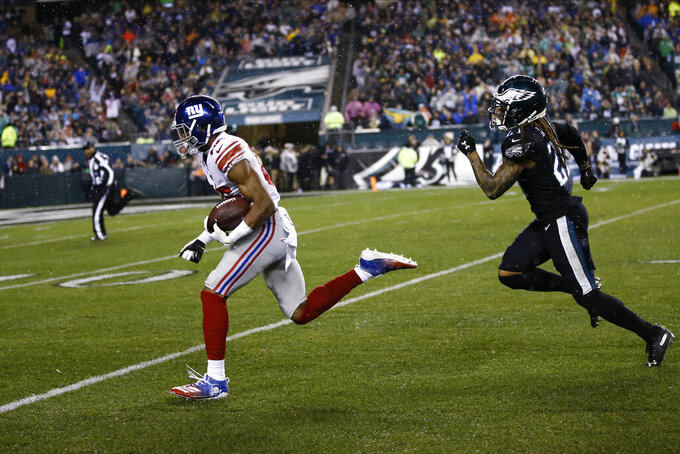 New York Giants' Darius Slayton, left, runs past Philadelphia Eagles' Ronald Darby to score a touchdown during the first half of an NFL football game, Monday, Dec. 9, 2019, in Philadelphia. (AP Photo/Michael Perez)