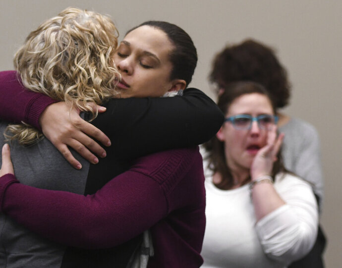Former youth gymnast Michelle Lippert hugs former Michigan State gymnastics coach Kathie Klages, Friday, Feb. 14, 2020, in Lansing, Mich., during a recess following Klages' testimony in her own trial. Lippert gave testimony the day before. A jury on Friday found Klages guilty of lying to police when she denied that two teen athletes told her of sexual abuse by sports doctor Larry Nassar in 1997, nearly 20 years before he was charged.  She faces up to four years in prison. (Matthew Dae Smith/Lansing State Journal via AP)