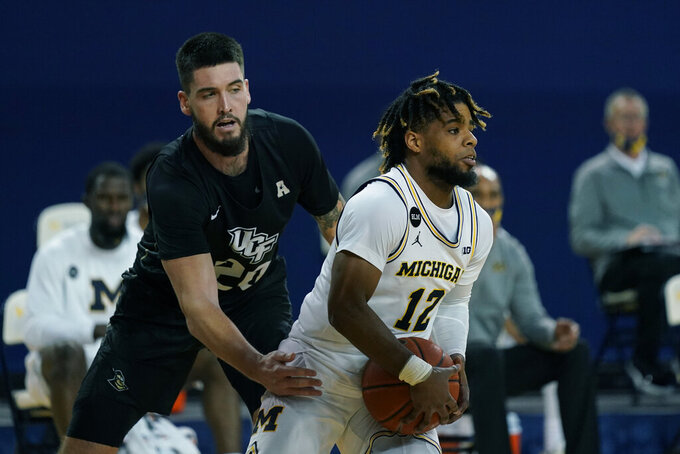 Central Florida forward Sean Mobley (20) reaches in against Michigan guard Mike Smith (12) during the second half of an NCAA college basketball game, Sunday, Dec. 6, 2020, in Ann Arbor, Mich. (AP Photo/Carlos Osorio)