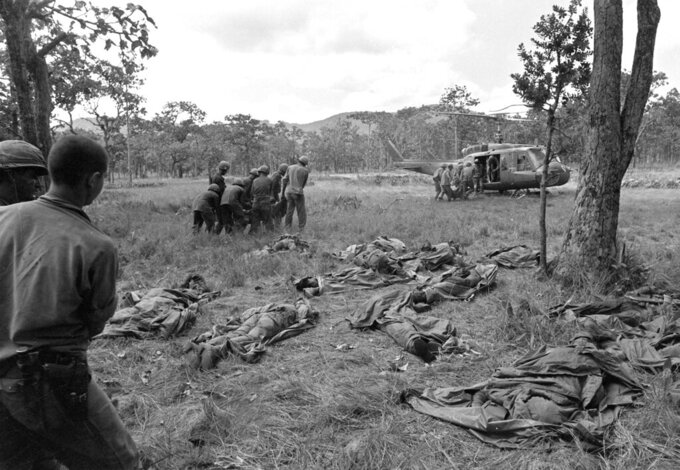 FILE - In this Nov. 18, 1965 file photo, U.S. troops carry bodies of air cavalrymen to an evacuation helicopter as more bodies lie on the ground at the site of an ambush by communist forces in the Ia Drang valley in Vietnam. In April 2020, the U.S.' coronavirus death toll surpassed the 58,220 American service members killed in Vietnam,which suffered over one million civilian and military deaths during the war. Vietnam has reported no COVID-19 deaths and less than 300 virus infections. (AP Photo/Rick Merron)