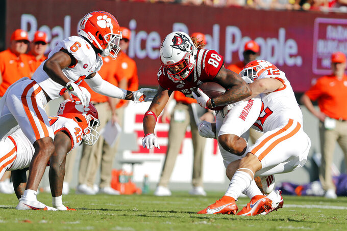 North Carolina State's Devin Carter (88) is tied up by Clemson's Tyler Venables (12) and Clemson's Tre Williams (8) during the first half of an NCAA college football game in Raleigh, N.C., Saturday, Sept. 25, 2021. (AP Photo/Karl B DeBlaker)