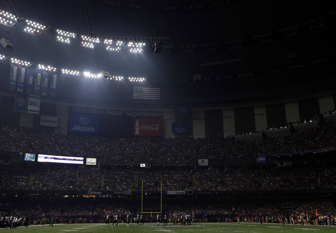FILE - In this Feb. 3, 2013, file photo, half the lights are out in the Superdome during a power outage in the second half of the NFL Super Bowl XLVII football game between the San Francisco 49ers and Baltimore Ravens, in New Orleans. For 34 minutes, the players, coaches and fans loitered in semi-darkness. (AP Photo/Marcio Sanchez, File)