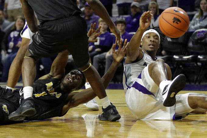 Kansas State's Xavier Sneed, left and Alabama State's Leon Daniels (1) chase a loose ball during the first half of an NCAA college basketball game Wednesday, Dec. 11, 2019, in Manhattan, Kan. (AP Photo/Charlie Riedel)