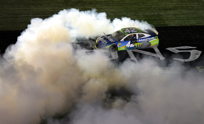 Kyle Larson does a burnout after winning the NASCAR All-Star Race at Charlotte Motor Speedway in Concord, N.C., Saturday, May 18, 2019. (AP Photo/Mike McCarn)