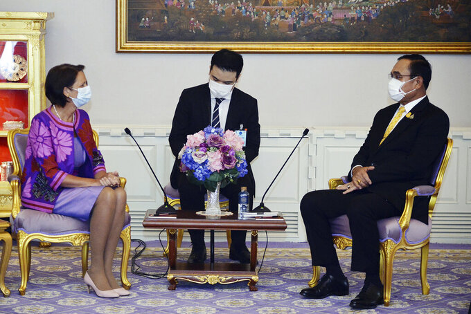In this photo released by Government Spokesman Office, United Nations Special Envoy to Myanmar Christine Schraner Burgener, left, talks with Thailand's Prime Minister Prayuth Chan-ocha, right, during a meeting at Government House in Bangkok, Thailand, Friday, May 14, 2021. (Government Spokesman Office via AP)