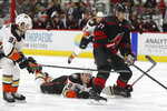 Carolina Hurricanes right wing Nino Niederreiter (21), of the Czech Republic, controls the puck while Anaheim Ducks defenseman Josh Manson (42) and defenseman Jacob Larsson (32) defend during the second period of an NHL hockey game in Raleigh, N.C., Friday, Jan. 17, 2020. (AP Photo/Gerry Broome)