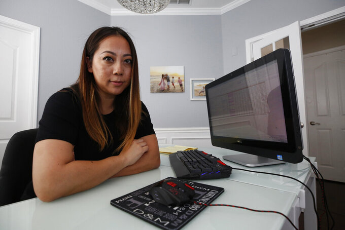 Mia Foster poses in her home office in Elk Grove, Calif., Friday, May 22, 2020. Foster, 37, was furloughed from her job providing IT services to health clinics on March 25, and waited five weeks to receive her unemployment benefits. California's unemployment rate nearly tripled to 15.5% in April because of the economic fallout from the coronavirus pandemic. (AP Photo/Rich Pedroncelli)