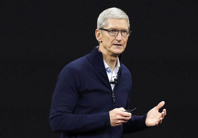 FILE- In this Sept. 12, 2017, file photo, Apple CEO Tim Cook, shows new Apple Watch Series 3 product at the Steve Jobs Theater on the new Apple campus in Cupertino, Calif. Cook is leaving shareholders in suspense about whether the iPhone maker will use its windfall from a tax cut on overseas profits for a big boost to its quarterly dividend. (AP Photo/Marcio Jose Sanchez, File)