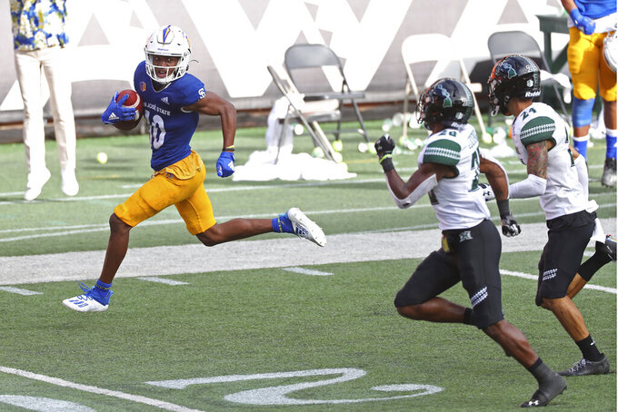 San Jose State wide receiver Tre Walker (10) looks back at Hawaii defensive backs Cameron Lockridge (20) and Kai Kaneshiro (24) as he runs into the end zone for a touchdown in the second half of an NCAA college football game Saturday, Dec. 5, 2020, in Honolulu. (AP Photo/Marco Garcia)