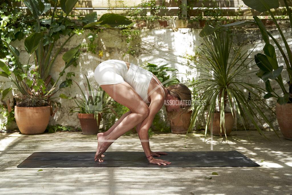 Woman balancing while practicing yoga in garden