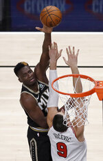 Atlanta Hawks' Clint Capela, left, shoots over Chicago Bulls' Nikola Vucevic (9) during the first half of an NBA basketball game Friday, April 9, 2021, in Atlanta. (AP Photo/Ben Margot)