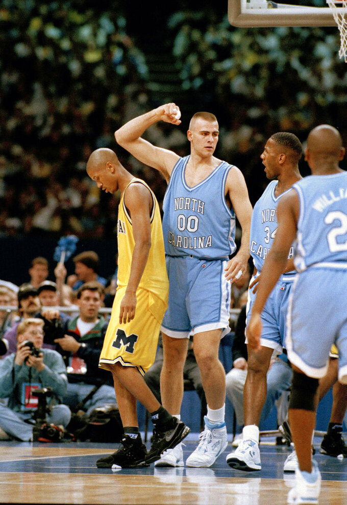 FILE - In this April 5, 1993, file photo, North Carolina's Eric Montross (00) and George Lynch celebrate a basket as Michigan's Jalen Rose, left, walks away during first half of their NCAA Final Four championship game at the Superdome in New Orleans. North Carolina beat Michigan 77-71. (AP Photo/Susan Ragan, Fle)