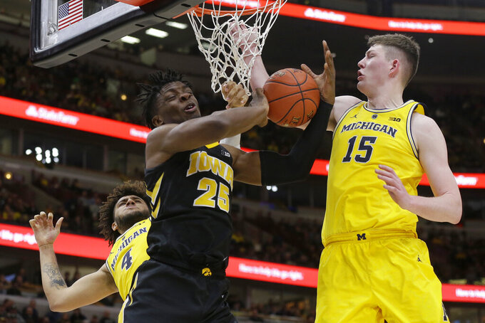 Michigan's Isaiah Livers (4) and Jon Teske (15) block a shot by Iowa's Tyler Cook (25) during the second half of an NCAA college basketball game in the quarterfinals of the Big Ten Conference tournament, Friday, March 15, 2019, in Chicago. (AP Photo/Kiichiro Sato)