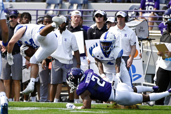 Northwestern defensive back Cameron Mitchell (2) upends Indiana State running back Matt Sora (25) during the first half of an NCAA college football game in Evanston, Ill, Saturday, Sept.11, 2021. (AP Photo/Matt Marton)
