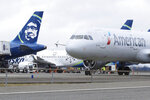 An American Airlines plane taxis past a parked Alaska Airlines plane, Thursday, Feb. 13, 2020, at Seattle-Tacoma International Airport in Seattle. American Airlines and Alaska Airlines announced Thursday that they will cooperate more closely on West Coast service, including new American flights from Seattle to India's technology hub in Bangalore. (AP Photo/Ted S. Warren)