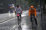 Two cyclists ride along the Embankment in central London,  Sunday July 25, 2021. Thunderstorms bringing lightning and torrential rain to the south are set to continue until Monday it is forecast. (Victoria Jones/PA via AP)