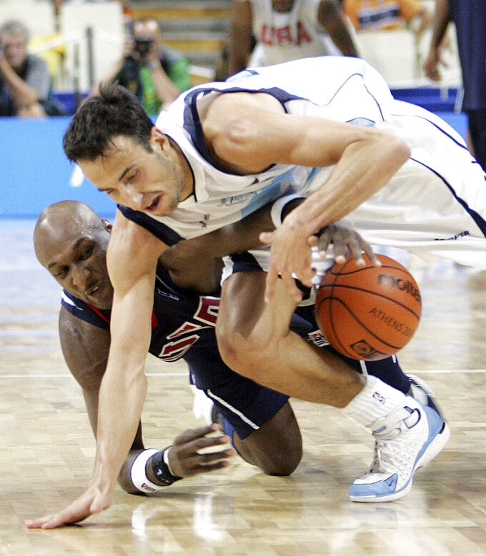 FILE - In this Aug. 27, 2004, file photo, Argentina's Emanuel Ginobili, top, battles the USA's Lamar Odom for the ball late in the fourth quarter of semifinal basketball game at the Olympic Indoor Hall during the 2004 Olympics in Athens, Greece. (AP Photo/Michael Conroy, File)