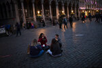Spanish Erasmus students sit and eat waffles on Grand Place during an autumn evening prior to the curfew in downtown Brussels, Friday, Oct. 23, 2020. (AP Photo/Francisco Seco)