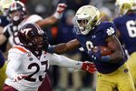 FILE - In this Nov. 2, 2019, file photo, Notre Dame running back Jafar Armstrong (8) stiff arms Virginia Tech linebacker Rayshard Ashby (23) during the second half of an NCAA college football game in South Bend, Ind. The Atlantic Coast Conference and Notre Dame are considering whether the Fighting Irish will give up their treasured football independence for the 2020 season play as a member of the league. (AP Photo/Carlos Osorio, File)