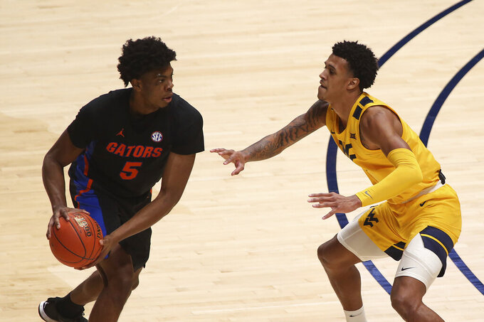 Florida forward Omar Payne (5) is defended by West Virginia forward Jalen Bridges (2) during the first half of an NCAA college basketball game Saturday, Jan. 30, 2021, in Morgantown, W.Va. (AP Photo/Kathleen Batten)