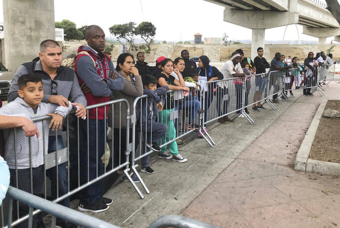 FILE - In this Thursday, Sept. 26, 2019 file photo asylum seekers in Tijuana, Mexico, listen to names being called from a waiting list to claim asylum at a border crossing in San Diego. A federal judge has ruled that a partial ban on asylum doesn't apply to anyone who appeared at an official border crossing before July 16 to make a claim, a move that could spare thousands of people. The administration said in July that it would deny asylum to anyone who traveled through another country without applying there first. The ban was on hold until the U.S. Supreme Court decided in September that it could take effect during a legal challenge. (AP Photo/Elliot Spagat,File)