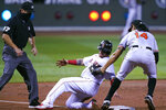 Baltimore Orioles' Rio Ruiz (14) tags out Boston Red Sox's Christian Vazquez, center, on a steal attempt at third base during the second inning of a baseball game at Fenway Park in Boston, Thursday, Sept. 24, 2020. At left is umpire Ben May. (AP Photo/Charles Krupa)
