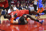 Houston Rockets center Clint Capela, top, falls over Oklahoma City Thunder center Steven Adams during the first half of an NBA basketball game, Monday, Jan. 20, 2020, in Houston. (AP Photo/Eric Christian Smith)