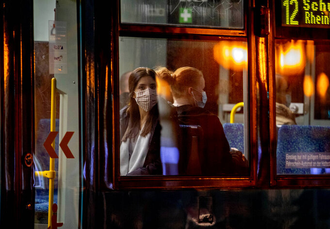 Two women wear face masks as the use a tram in Frankfurt, Germany, early Monday, Oct. 19, 2020. (AP Photo/Michael Probst)