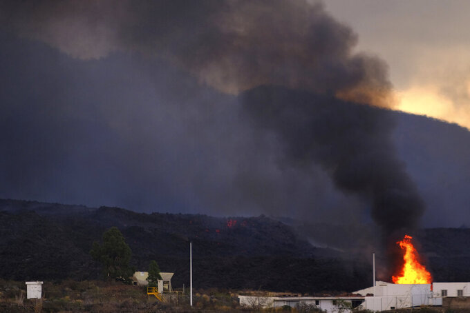 A house is burnt by the lava on the Canary island of La Palma, Spain, on Wednesday, Oct. 13, 2021. A new river of lava has belched out from the La Palma volcano, spreading more destruction on the Atlantic Ocean island where molten rock streams have already engulfed over 1,000 buildings. The partial collapse of the volcanic cone has sent a new lava stream heading toward the western shore of the island. (AP Photo/Daniel Roca)