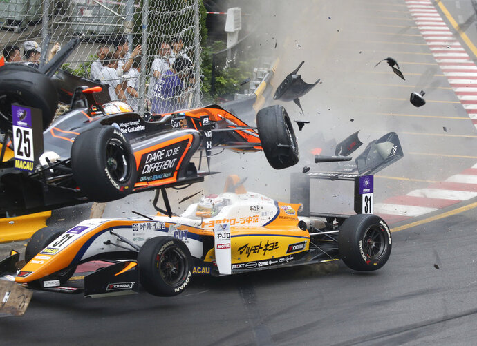 In this Sunday, Nov. 18, 2018, picture, teenage driver Sophia Floersch of Germany, top, goes over Japanese driver Sho Tsuboi's car while flying off the track at high speed on a tight right-hand bend on lap four. Floersch will undergo surgery for a spinal fracture after a spectacular airborne crash in the Formula 3 Macau Grand Prix on Sunday. (Tony Wong/Apple Daily via AP)