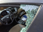 This Thursday, May 21, 2020, photo shows a parked car with a broken front window after a smash-and-grab break-in in Los Angeles. The coronavirus hasn't been kind to car owners. With more people than ever staying home to lessen the spread of COVID-19, their sedans, pickup trucks and SUVs are parked unattended on the streets, making them easy targets for opportunistic thieves.    (AP Photo/Damian Dovarganes)