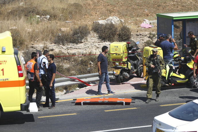 Israeli security and emergency services stand at the scene of an car ramming attack near Gush Etzion settlement cluster in the West Bank, Friday, Aug. 17, 2019. The Israeli military says a Palestinian driver has been shot and killed after he rammed his car and injured two Israelis in the West Bank. (AP Photo/Mahmoud Illean)