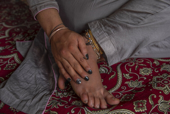 Transgender Kashmiri Khushi Mir rests in her rented room on the outskirts of Srinagar, Indian controlled Kashmir, Friday, June 4, 2021. Until the pandemic, singing and dancing at weddings used to earn Mir enough income to take care of her family. Unable to pay for her rented accommodation, the 19-year-old took a job as a construction worker for 15 days that paid $9.60 a day. Mir has set up a charity, along with four friends, to distribute food kits to members of the transgender community. (AP Photo/ Dar Yasin)