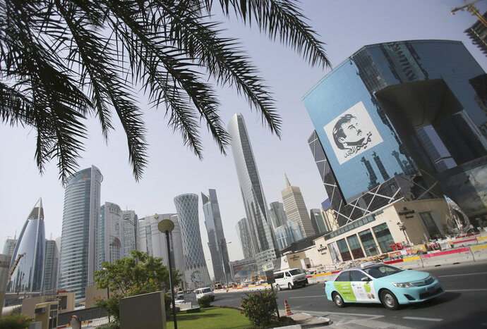 FILE - In this May 5, 2018, file photo, a taxi passes by a building with an image of emir of Qatar, Sheikh Tamim bin Hamad Al Thani, in Doha, Qatar. Amnesty International is accusing a contractor involved in building a stadium for the 2022 FIFA World Cup of not paying its workers. The rights group released a report Wednesday, Sept. 26, 2018, that alleges engineering firm Mercury MENA owes thousands of dollars of wages to workers from countries where most live on less than $2 a day. (AP Photo/Kamran Jebreili, File)